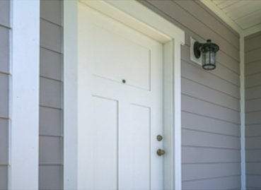 A front door surrounded by grey siding in Bloomington IL