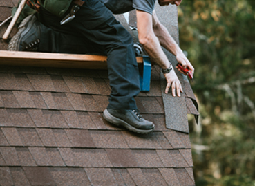 Roofer in Bloomington IL repairing the corner of a roof