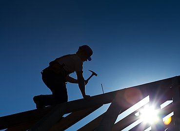 Roofing Contractors in Peoria IL hammering nails into a roof