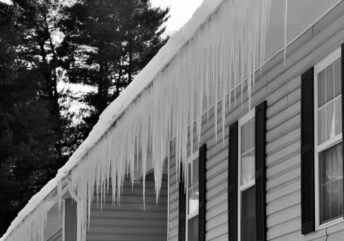 Icicles hanging off a roof due to gutter needing cleaning