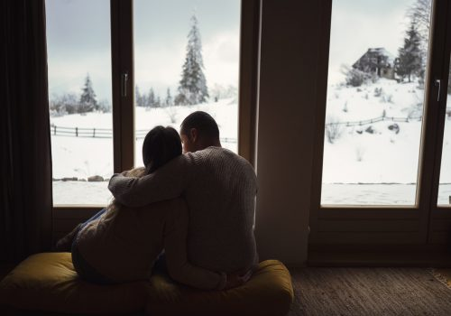 Couple sitting in front of a window looking at the snow
